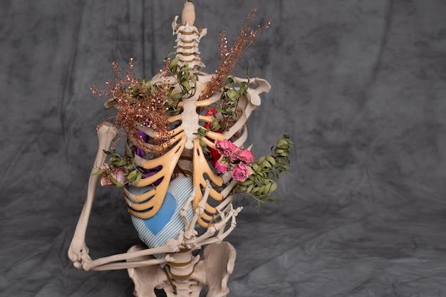 Menschliches skelett auf grauem hintergrund mit blumen im inneren