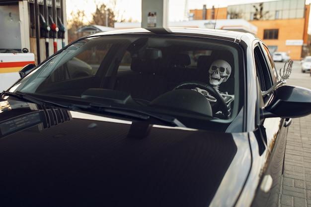 Menschliches skelett im auto, tanken an tankstelle, nachfüllen von kraftstoff. benzin-, benzin- oder dieseltankservice, benzintanken