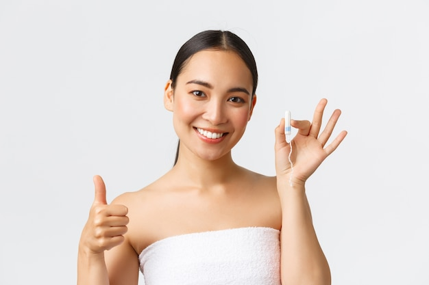 Menstruationshygienekonzept für schönheit, körperpflege und intimpflege. nahaufnahme der schönen jungen asiatischen frau im badetuch, das tampon und daumen oben zeigt, auf ihrem peirod, weißen hintergrund.