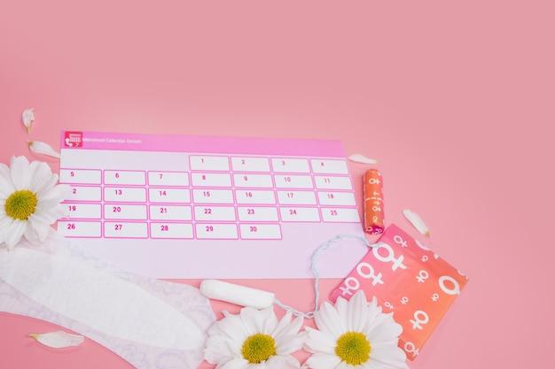 Menstruationskalender mit baumwoll-tampons damenbinden, weiße blume