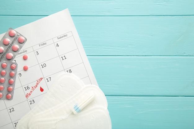 Menstruationskalender mit tampons und pads aus baumwolle auf blauem hintergrund. frauenkritische tage, frauenhygieneschutz. menstruationsbeschwerden
