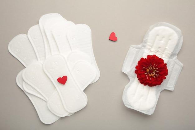 Menstruationspads auf grauem hintergrund. eine rosenblüte liegt auf einer menstruationsunterlage. menstruationszyklus. hygiene und schutz. ansicht von oben.