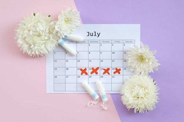 Menstruationstampons auf menstruationsperiodenkalender mit weißen blumen