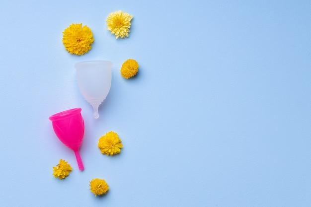 Menstruationstasse mit blumen auf blauem hintergrund
