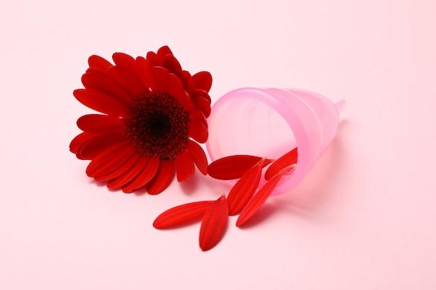 Menstruationstasse und gerbera auf rosa oberfläche, nahaufnahme