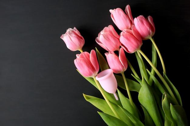 Menstruationstasse und rosa tulpen auf einem schwarzen hintergrund. frauengesundheit.