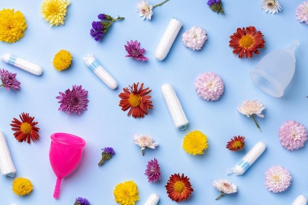 Menstruationstasse und tampons auf blumenmusteroberfläche