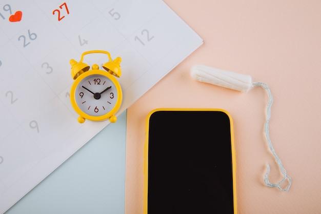 Menstruationszyklus-konzept. kalender für den monat mit markierungen und einer mobilen anwendung auf dem smartphone-bildschirm.