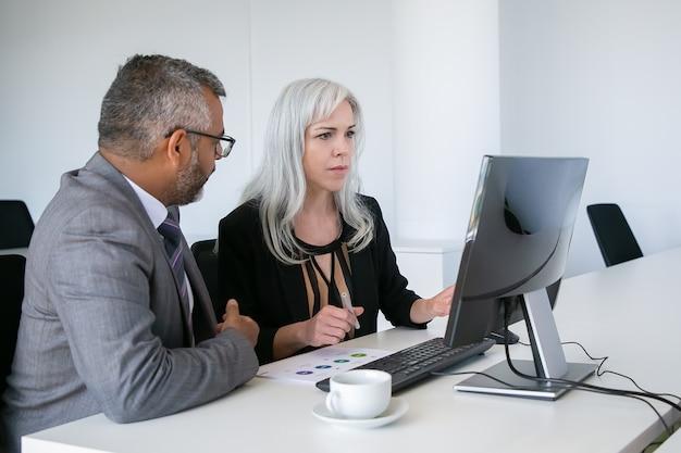 Mentor hilft praktikant am arbeitsplatz. kollegen beobachten inhalt auf pc-monitor, sitzen am tisch mit papierdiagramm. geschäftskommunikationskonzept