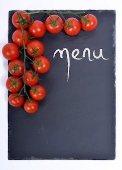 Menü auf einer tafel mit tomaten