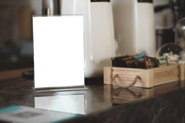 Menü-kartenhalter mit weißem blatt papier auf tabelle im café