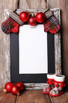 Menübrett mit weihnachtsdekoration auf hölzernem plankenhintergrund