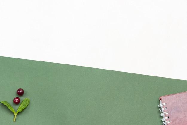 Menühintergrund zweig der minze preiselbeeren und frühlingsnotizbuch auf grün