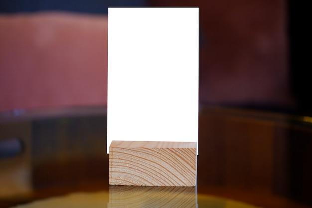 Menürahmen, der auf hölzerner tabelle im barrestaurantcafé steht
