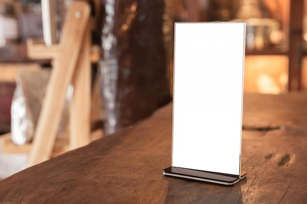 Menürahmen, der auf hölzerner tabelle in der kaffeestube steht. platz für textmarketing-werbung
