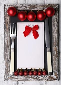 Menütafel mit weihnachtsdekoration auf holzplankenoberfläche