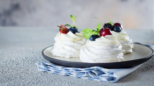 Meringenachtisch pavlova-kuchen mit frischen beeren auf einer platte.