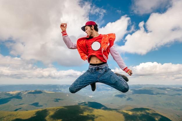 Merkwürdige seltsame ungewöhnliche glückliche männliche person, die in himmel springt. reisendmann, der elektronische zigarette auf berg raucht. junges rebellenjungenporträtfliegen in den wolken. freizeitbeschäftigung im freien. szenische ansicht