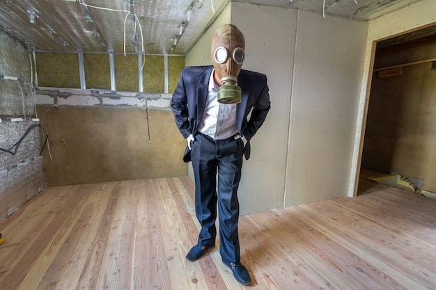Merkwürdiger mann in der geschäftsmannklage und in der gasschutzmaske innerhalb eines raumes unter erneuerungsarbeiten.