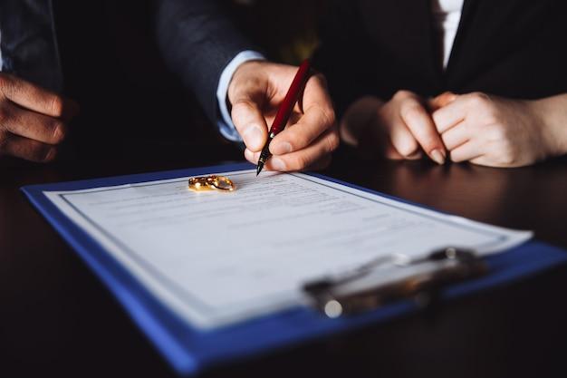 Merriage scheidungsprozess. trennung der ehegatten im kabinett des anwalts. leute unterzeichnen vereinbarung.