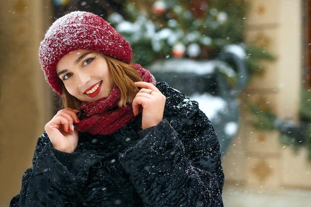 Merrybrunette-frau mit roten lippen mit roter mütze und schal, die während des schneefalls in der stadt spazieren geht. freiraum