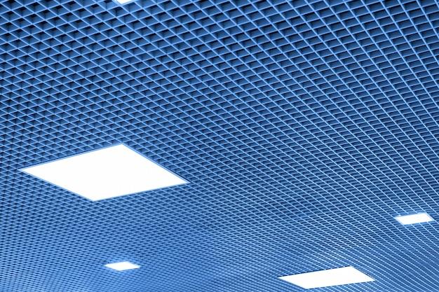 Mesh abgehängte decke mit fluoreszierenden oder led quadratischen lichtern in modernen einkaufszentrum oder bürogebäude