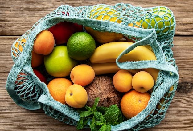 Mesh-einkaufstasche mit bio-früchten auf holzhintergrund. flache lage, draufsicht. kein abfall, kunststofffreies konzept. sommerfrüchte.