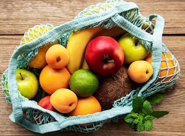 Mesh-einkaufstasche mit bio-früchten auf holztisch. flache lage, draufsicht. kein abfall, kunststofffreies konzept. sommerfrüchte.