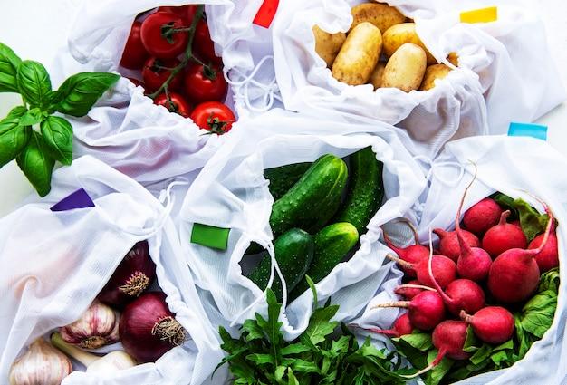 Mesh-einkaufstasche mit bio-gemüse auf marmortisch. flache lage, draufsicht. kein abfall, kunststofffreies konzept. sommerfrüchte.