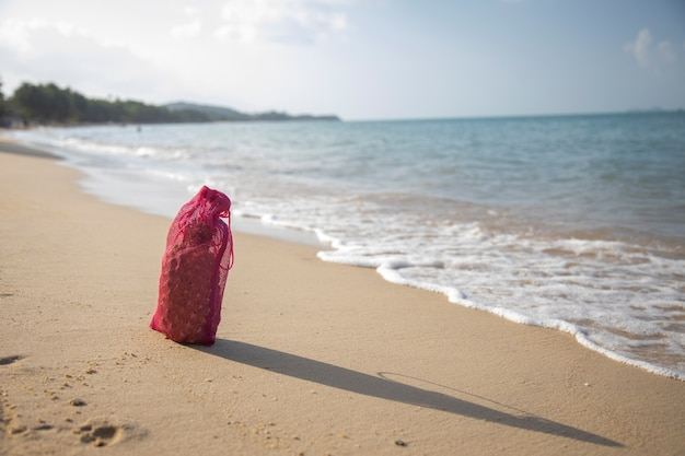 Mesh-einkaufstasche mit früchten steht an einem sonnigen tag am sandstrand des meeres. ökologie des ozeans konzept