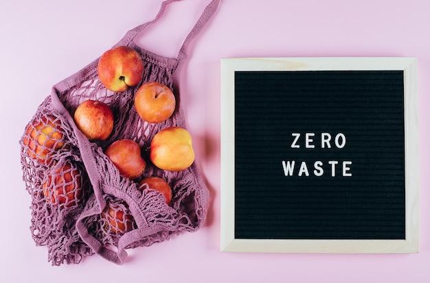 Mesh-einkaufstasche mit früchten und buchstaben tafel mit text zero waste auf rosa.
