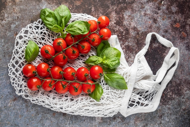 Mesh-einkaufstasche mit tomaten und basilikum