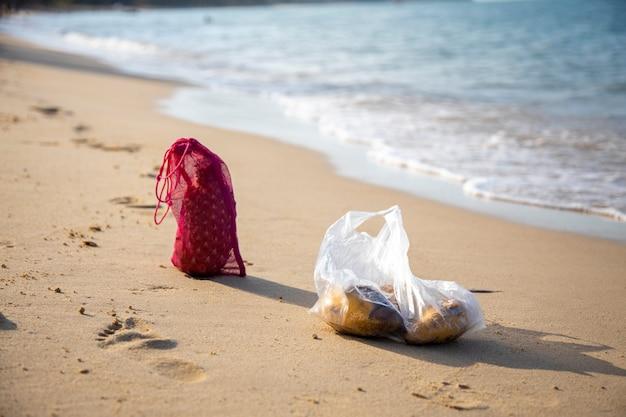 Mesh-einkaufstasche und plastiktüte liegen an einem sonnigen tag am sandstrand des meeres. ökologie der ozeane konzept