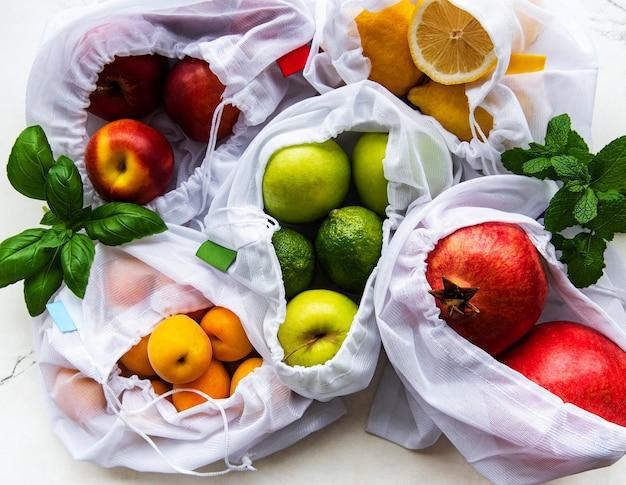 Mesh-einkaufstaschen mit bio-früchten auf marmoroberfläche