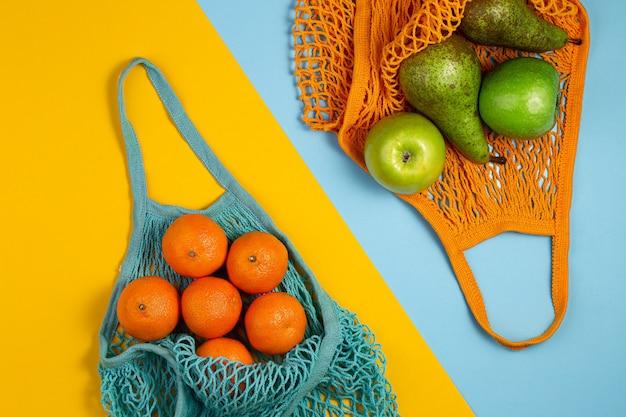 Mesh textil tasche voller bunter früchte. gesundes essen und null-abfall-konzept