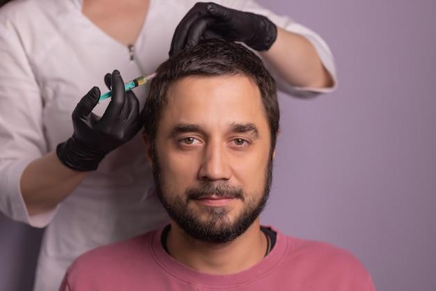 Mesotherapie für haare. attraktiver mann, der injektionen in seinen kopf erhält. mann mit mesotherapie-sitzung im schönheitssalon, therapeut im schutzhandschuh mit spritze,