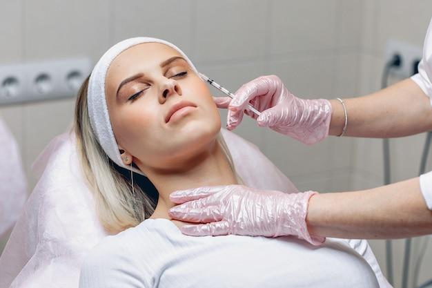 Mesotherapie. kosmetikerin, die kosmetische eingriffe mit einer spritze im gesicht eines jungen kunden durchführt.
