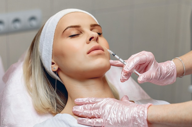 Mesotherapie. schöne kosmetikerin, die kosmetische eingriffe mit einer spritze im gesicht eines jungen kunden durchführt.