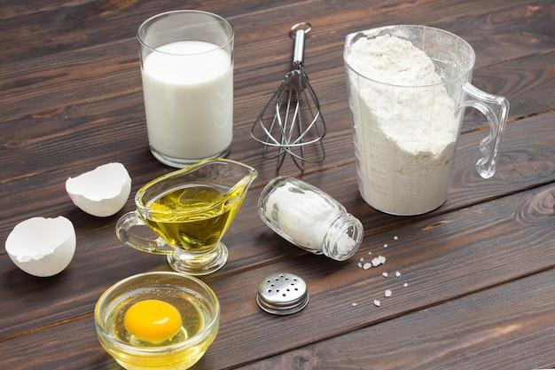 Messbecher mit mehl, glas milch, zerbrochenem ei und salz, metallbesen auf dem tisch. dunkle holzoberfläche. draufsicht