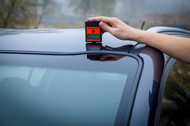 Messen der dicke der autolackbeschichtung in schwarzer farbe mit einem lackdickenmesser.