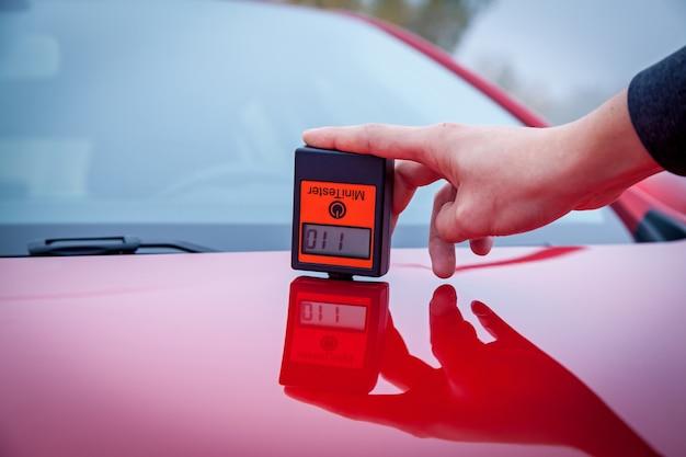 Messen der dicke der roten farbe der autolackbeschichtung mit einem lackdickenmesser.