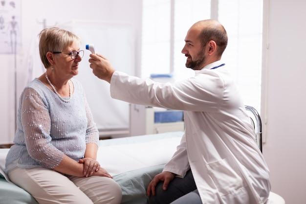 Messen der temperatur der alten älteren frau während der konsultation im untersuchungsraum der klinik