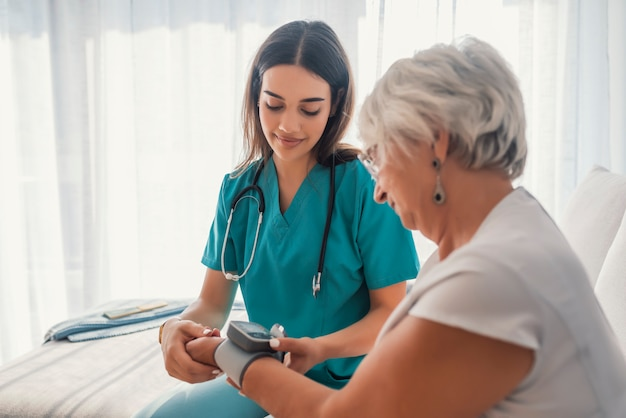 Messender blutdruck der jungen krankenschwester der älteren frau zu hause.
