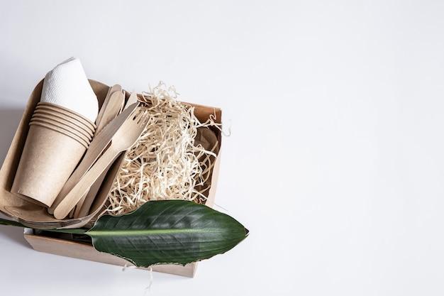 Messer, gabeln, tassen, papierbehälter für lebensmittel und ein natürliches blatt. das konzept von null abfall und plastikfrei.