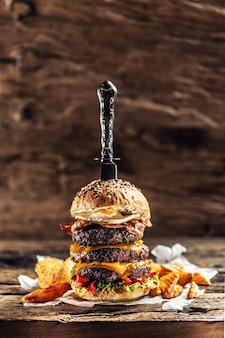 Messer gestochen in einem dreifachen cheeseburger mit rindfleischpatty, geschmolzenem käse, ei und paprika in einer rustikalen holzumgebung.