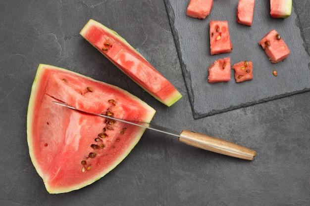 Messer in fruchtfleisch reifer wassermelone. scheibe wassermelone auf dem tisch. schneiden von wassermelonenpulpe auf schneidebrett. flach liegen. schwarzer hintergrund