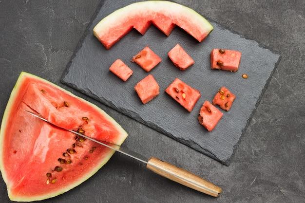 Messer in fruchtfleisch reifer wassermelone. schneiden von wassermelone auf schneidebrett. flach liegen. schwarzer hintergrund