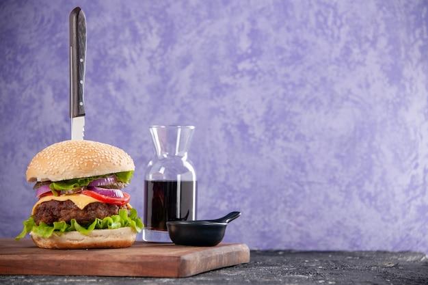 Messer in leckerem fleisch-sandwich-sauce-ketchup auf holzbrett auf der rechten seite auf isolierter eisfläche mit freiem platz