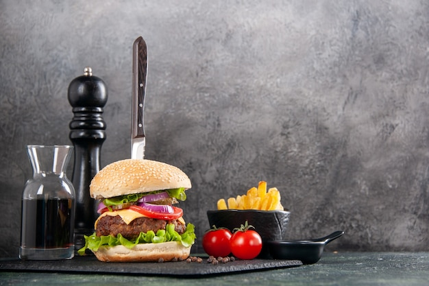 Messer in leckerem fleischsandwich und grünem pfeffer auf schwarzer tablettsauce ketchup-tomaten mit stielpommes auf der rechten seite auf dunkler oberfläche