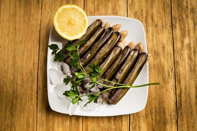 Messer, petersilie und eine halbe zitrone in weißen schüsseln mit eis